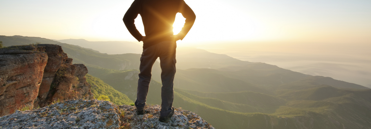 A fit man at the top of a peak after a climb