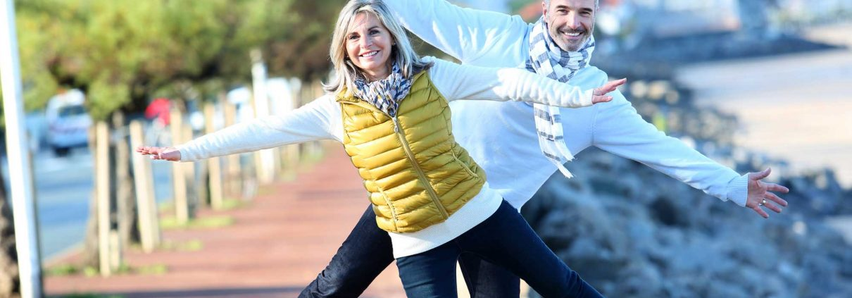 An attractive, smiling couple exercising outdoors