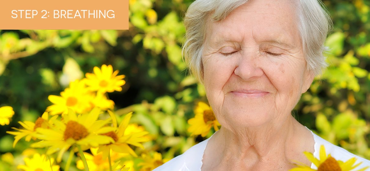 A mature woman, relaxing in a garden and practicing breathing for pain care management and control