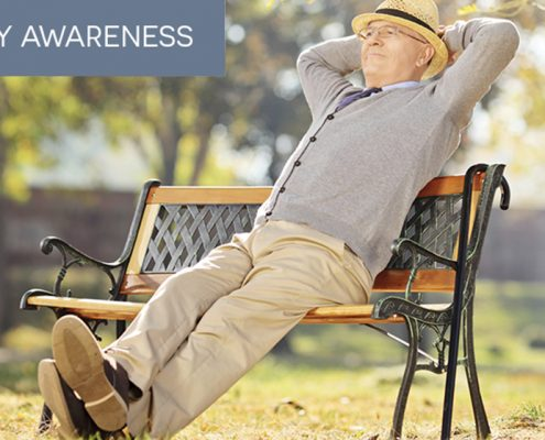 A smiling, mature man stretching on a park bench, practicing stretching for pain care management and control