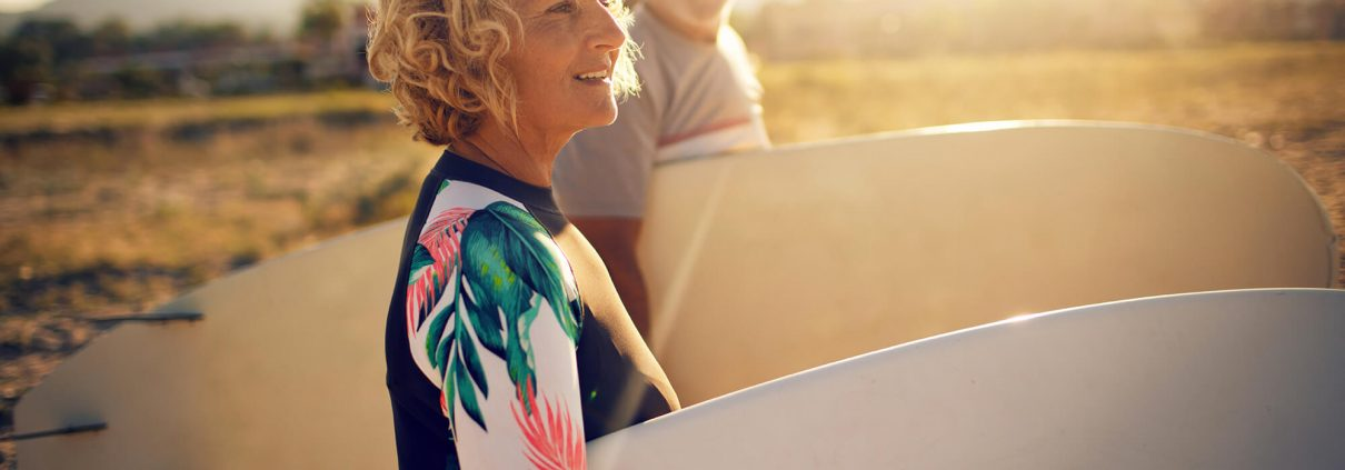 Two seniors on the beach with surfboards, a smiling, attractive man and woman